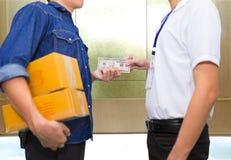 Рука человека держит американские деньги и оплату доллара для ord пакета Стоковые Изображения