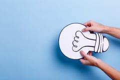 Рука человека держит обратное изображение электрической лампочки Голубая предпосылка с местом для надписи стоковое изображение
