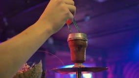 Рука человека изменяет угли в кальяне Комната освещена с голубым светом сток-видео