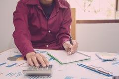 рука человека используя калькулятор высчитывая bonusOr другая компенсация к работникам для увеличения урожайности Писчая бумага н стоковое изображение