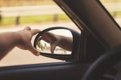 рука человека исправляет бортовое зеркало в автомобиле, ретро тонизировать Стоковые Изображения RF