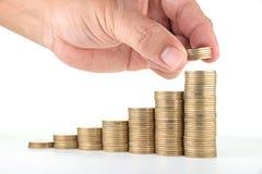 Рука человека кладя деньги к поднимая стогам монетки на белую предпосылку Стоковое Изображение