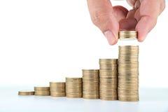 Рука человека кладя деньги к поднимая стогам монетки на белую предпосылку Стоковая Фотография RF
