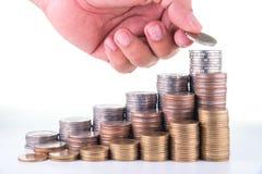 Рука человека кладя деньги к поднимая стогам монетки на белую предпосылку Стоковое фото RF