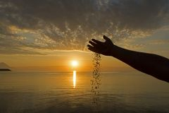 Рука человека льет песок на предпосылке восхода солнца стоковая фотография rf
