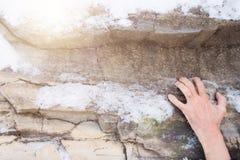 Рука человека льнет к уступу на камне покрытый снежок утеса стоковые фото