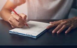 Рука человека пишет памятку на календаре стоковое фото rf