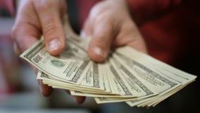 Рука человека показывая банкноты доллара Закройте вверх американских денег наличных денег в мужских руках видеоматериал