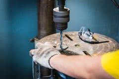 Рука человека работника сверлит отверстие в железном кронштейне с dri штендера Стоковые Изображения RF