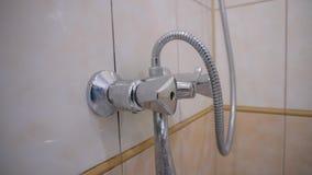Рука человека раскрывает водопроводный кран в bathroom и закрывает ее назад Конец-вверх руки экрана и человека сток-видео