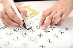 Рука человека с календарем и черной отметкой Метка концепции на календаре стоковое изображение