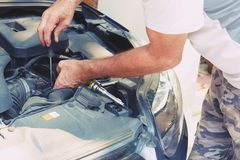 Рука человека с отверткой проверяя двигатель автомобиля стоковое фото