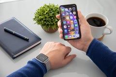 Рука человека с серией 4 дозора Яблока и iPhone x стоковое изображение