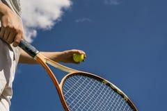 Рука человека теннисиста делая съемку держа шарик и ракетку против неба стоковое фото rf