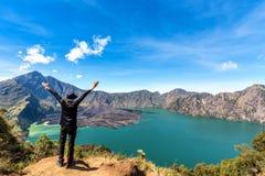 Рука человека Hiker распространяя и наслаждается с вулканом Baru Jari, озером Segara Anak после законченный взбираться на горе Ri Стоковое Изображение RF