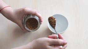 Рука черпая растворимый кофе ложкой от стеклянного опарника в чашке сток-видео
