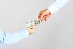 Рука человека дает американцу денег 100 долларовых банкнот к руке мальчика Стоковая Фотография
