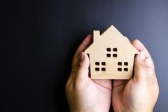 Рука человека держа деревянную игрушку дома на черной предпосылке с полисменом Стоковая Фотография