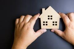 Рука человека держа деревянную игрушку дома на черной предпосылке с полисменом Стоковые Изображения RF