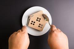 Рука человека держа ложку и вилку черпая деревянный дом в a Стоковые Изображения