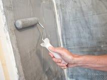 Рука человека держа paintbrush ролика Стоковое Изображение