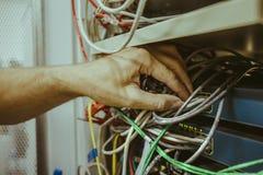 Рука человека инженера соединяет кабель сети к переключателю эпицентра деятельности оптического волокна для цифровых связей в ком Стоковая Фотография RF