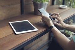 рука человека используя smartphone с цифровой таблеткой Стоковое фото RF