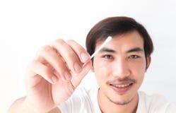 Рука человека крупного плана держа бутон хлопка для очищая уха, здоровья ca стоковые изображения