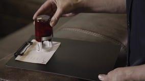 Рука человека кладет штемпель на бумагу в черную папку видеоматериал