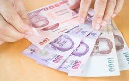 Рука человека подсчитывая банкноту тайского бата Стоковые Фото