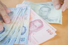 Рука человека подсчитывая банкноту тайского бата Стоковые Изображения
