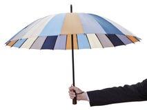 Рука человека с открытым striped зонтиком стоковые фото