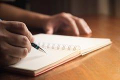 Рука человека с сочинительством ручки на тетради Стоковая Фотография RF