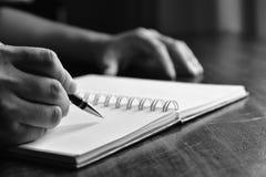 Рука человека с сочинительством ручки на тетради Стоковые Изображения RF