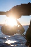 Рука человека с удя оборудованием в заходе солнца Стоковые Фотографии RF