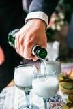 Рука человека льет шампанское в стекла стоковое изображение