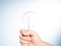 рука шарика держа раскаленный добела свет Стоковые Изображения