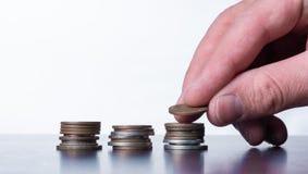 Рука штабелируя небольшие монетки на таблице стоковые изображения