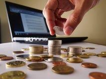 Рука штабелируя вверх по монеткам и портативному компьютеру Стоковая Фотография