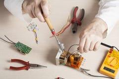 Рука электрика с зондом вольтамперомметра на электрическом шкафе switchgear Инструменты инженерства Стоковые Изображения