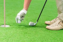 Рука людей в перчатке кладя шар для игры в гольф Стоковая Фотография