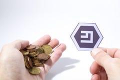 Рука Cryptocurrency держит монетки евро и composi emercoin стоковая фотография rf