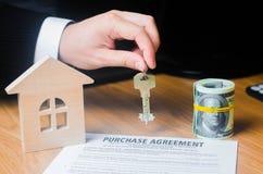 Рука ` s бизнесмена держит ключи к контракту для приобретения свойства или недвижимости Концепция контракта pur стоковые фотографии rf