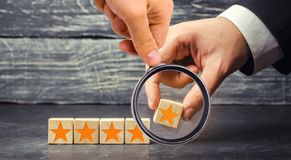Рука ` s бизнесмена держит пятую звезду Получите пятую звезду Концепция оценки гостиниц и ресторанов, стоковое изображение