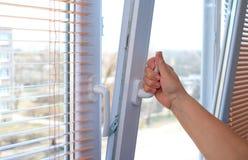 Рука ` s взрослой женщины раскрывая окно для вентиляции стоковое изображение rf
