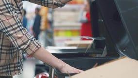 Рука ` s девушки в рубашке шотландки рассматривая гриль в магазине видеоматериал