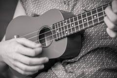 Рука ` s девушки тренькая гавайской гитарой сопрано стоковая фотография