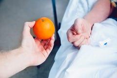 Рука ` s доктора держит апельсин против капельницы стоковое изображение rf