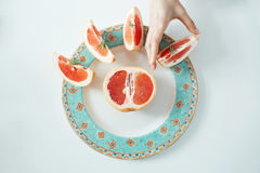 Рука ` s девушки принимая кусок грейпфрута от белой плиты От выше Питание здорового питания Стоковая Фотография