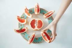 Рука ` s девушки принимая кусок грейпфрута от белой плиты От выше Питание здорового питания Стоковое Изображение